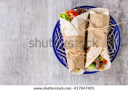Mexican style dinner. Two papered tortillas burrito with beef and vegetables served on blue ornamental ceramic plate over white wooden background. Flat lay. With copy space