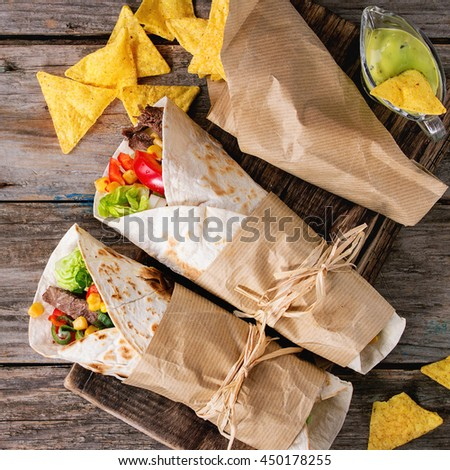 Mexican style dinner. Two papered tortillas burrito with beef and vegetables served with nachos chips and guacomole sauce over old wooden background. Flat lay. Square image