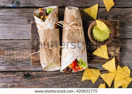Mexican style dinner. Two papered tortillas with beef and vegetables served with nachos chips and guacomole sauce over old wooden background. Flat lay With copy space
