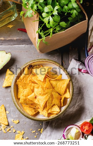 Mexican style dinner with tortilla, herbs, corn chips nachos  and guakomole, served over gray wooden table. Top view. - stock photo