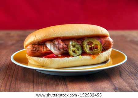 Mexican style hot dog with bacon, salsa, jalapeno and chili - stock photo