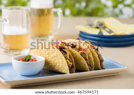 Mexican tacos with beef, cheddar cheese, tomato, beans and salsa dips at beer garden