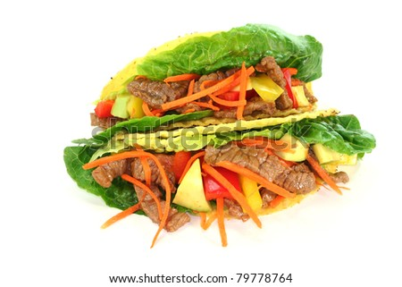Mexican tacos with beef, lettuce, peppers and avocado on white background - stock photo