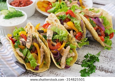 Mexican tacos with chicken, bell peppers, black beans and fresh vegetables - stock photo