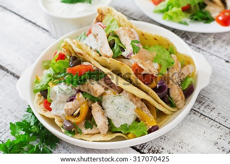 Mexican tacos with chicken, bell peppers, black beans and fresh vegetables and tartar sauce - stock photo