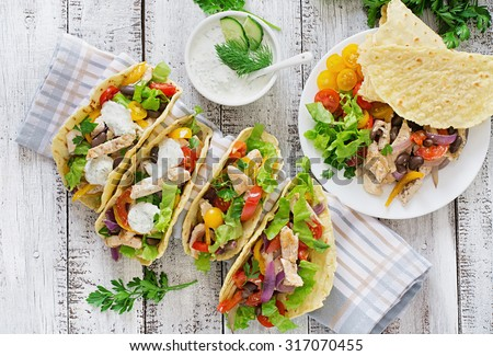Mexican tacos with chicken, bell peppers, black beans and fresh vegetables and tartar sauce. Top view - stock photo
