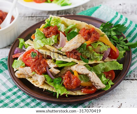 Mexican tacos with chicken, bell peppers, black beans and fresh vegetables and tomatoes sauce. - stock photo