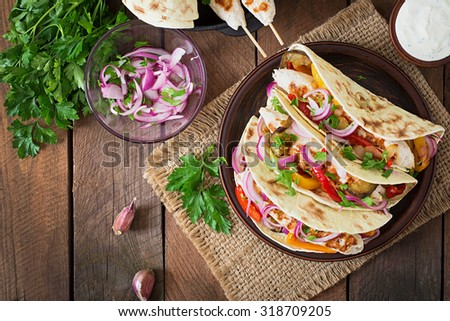 Mexican tacos with chicken, grilled vegetables and red onion. Top view