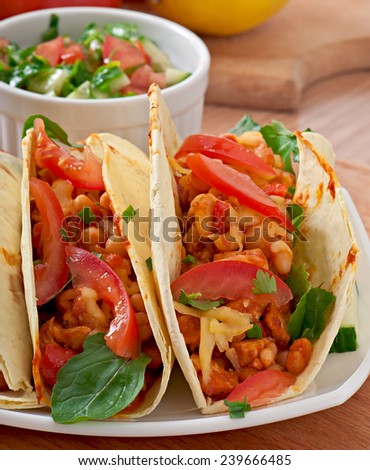 Mexican tacos with chicken, tomatoes and beans
