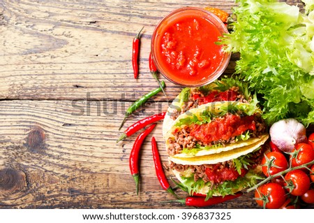 mexican tacos with meat and salsa on a wooden table, top view - stock photo