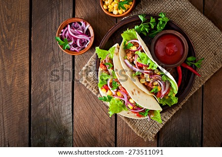 Mexican tacos with meat, vegetables and red onion. Top view - stock photo