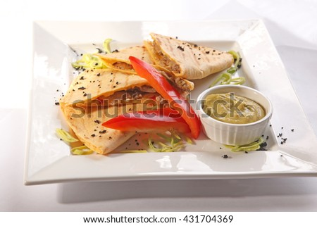 Mexican Tortilla with guacamole and pepper on plate - stock photo