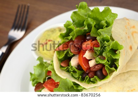 Mexican tortilla wraps filled with chicken, beans, tomato and lettuce with guacamole in the back (Selective Focus, Focus on the filling on the right)