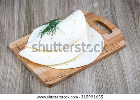 Mexican Tortillas with dill leaves on the wood background