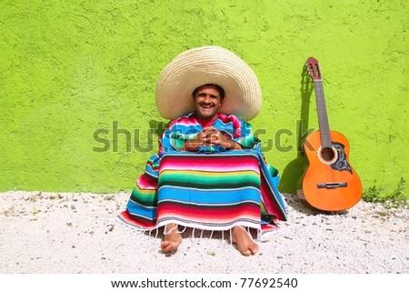 Mexican typical lazy topic man guitar poncho sit in green wall - stock photo