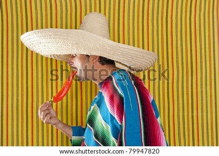 Mexican typical man eating chili hot pepper with poncho on yellow background - stock photo