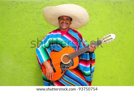 Mexican typical man playing guitar with poncho on green wall - stock photo