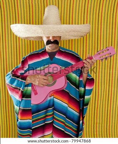 Mexican typical man with poncho and sombrero playing guitar - stock photo