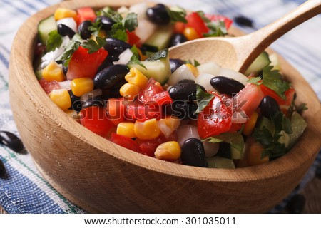 Mexican vegetable salad with black beans, avocado and corn close up in a wooden plate. horizontal - stock photo
