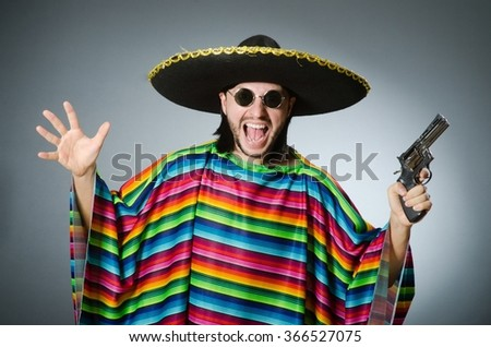 Mexican with gun wearing sombrero - stock photo
