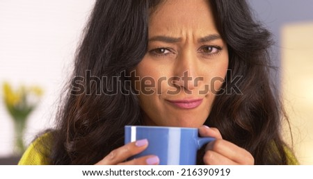 Mexican woman making a funny face with mug - stock photo