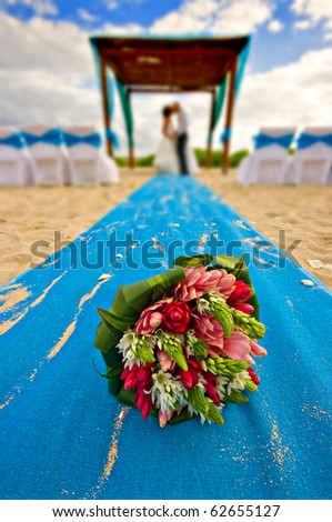 mexico beach wedding with bouquet in the foreground - stock photo