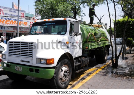 MEXICO CITY - APRIL 28: A water truck washes and cleans the street of Calzada de Tlalpan in front of a hospital in Mexico City, during the outbreak of the flu epidemic on April 28, 2009 in Mexico CIty. - stock photo