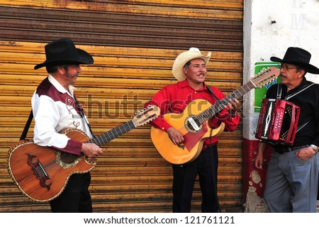 MEXICO CITY - FEB 28: Mariachi band play Mexican music at Xochimilco's Floating Gardens on February 28 2010 in Mexico City, Mexico.  It's Mexican musical tradition that dates back to the 19th century - stock photo