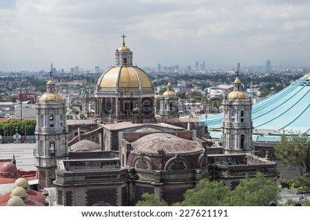 MEXICO CITY, MEXICO - OCTOBER 23, 2014: From Tepeyac Hill a good view is had of the old and new Basilica of Our Lady of Guadalupe as well as the Mexico City skyline in the distance. - stock photo