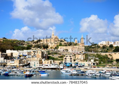 MGARR, GOZO, MALTA - APRIL 3, 2017 - View of boats in the harbour with the Ghajnsielem Parish church and Our lady of Lourdes church to the rear, Mgarr, Gozo, Malta, Europe, April 3, 2017.