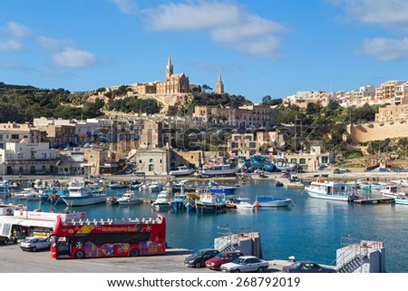 MGARR, MALTA - JANUARY 13, 2015: Mgarr harbour with view of church Our Lady of Lourdes on top of the hill, Gozo island. - stock photo