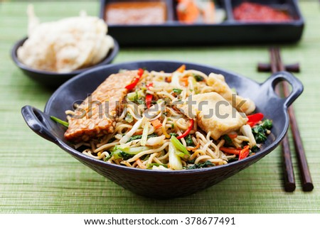 Mi goreng,mee goreng Indonesian cuisine, spicy stir fried noodles with tempeh and assortment of asian sauces - stock photo