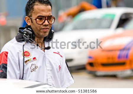 MIAMI - APRIL 18: Car technician waiting in the pits during the FARA races April 18, 2010 in Miami, Florida. - stock photo