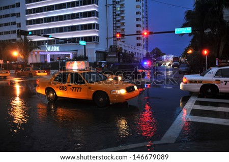 MIAMI BEACH, FL - JULY 18: Cars moving on flooded streets and roads of Miami South Beach  after heavy rains in Florida July 18, 2013 in Miami Beach, Florida - stock photo