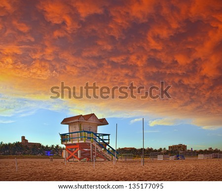 Miami Beach Florida, colorful lifeguard house in a typical Art Deco architecture, at sunset with red storm clouds in the sky - stock photo