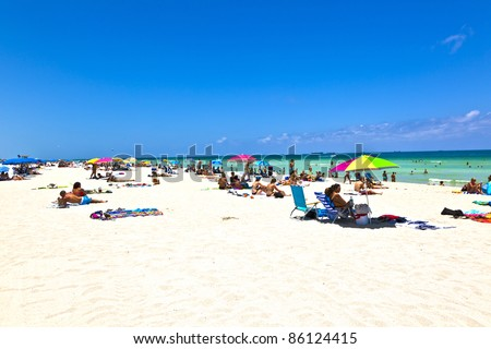MIAMI BEACH, FLORIDA - JULY 27: People enjoy swimming in South Beach on July 27,2010 in Miami Beach, Florida. In 1870, Henry and Charles Lum purchased the area and his daughter Taylor named it South Beach. - stock photo