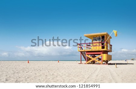 Miami Beach Florida, lifeguard house in typical colorful Art Deco style on a sunny summer day, with blue sky, and Atlantic Ocean in the background. World famous travel location.