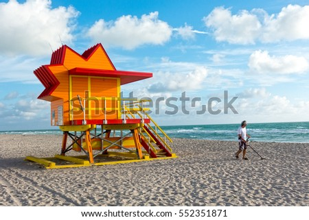MIAMI BEACH, FLORIDA/USA - DECEMBER 2016: Man Searching With Metal Detector Near Lifeguard Tower on the South Beach. Hunting For Hidden Treasure.
