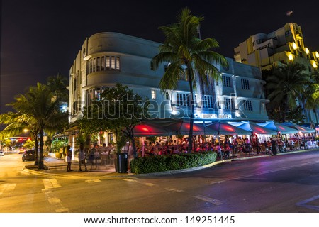 MIAMI BEACH - JULY 28: Night view at Ocean drive on July 28, 2013 in Miami Beach, Florida. Art Deco Night-Life in South Beach at Ocean Drive  is one of the main tourist attractions in Miami. - stock photo