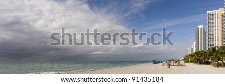 Miami Beach Landscape panorama of beach buildings in sunny morning while the stormy hurricane dark rain clouds are approaching from the sea, a typical summer occurrence in the tropics.   Copyspace. - stock photo