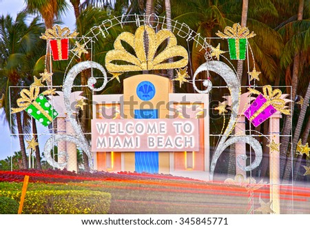 Miami Beach Welcome sign in Christmas holiday decorations and palm trees at sunset with moving traffic