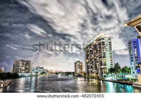 Miami buildings at night with river reflections.