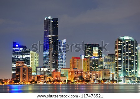 Miami city architecture closeup at dusk with urban skyscrapers over sea with reflection - stock photo