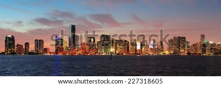 Miami city skyline panorama at dusk with urban skyscrapers over sea with reflection - stock photo