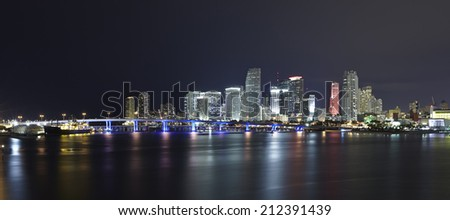 Miami city skyline panorama at night with urban skyscrapers and bridge over sea with reflection - stock photo