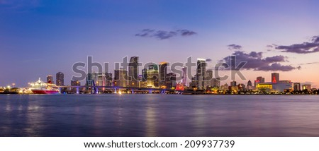 Miami city skyline panorama at twilight with urban skyscrapers and bridge