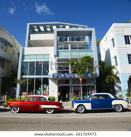 MIAMI - DEC 24: Excess Building with Art Deco Style and colorful antique cars in Miami Beach on December 24th, 2012 in Miami, Florida, USA. - stock photo