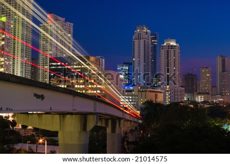 Miami Elevated Commuter Train Tracks and City Buildings at Night - stock photo