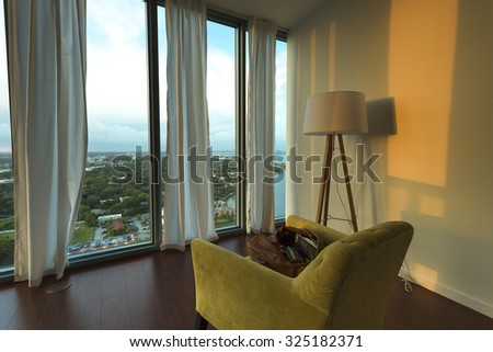 MIAMI, FL, AUGUST 21: Interior of a furnished apartment with view on Miami Beach. The furniture are only a chair and a lamp with open coman bag. USA 2012 - stock photo