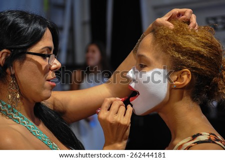 MIAMI, FL - JULY 20: A dancer getting readywith makeup backstage at the Luli Fama fashion show during MBFW Swim 2015 at The Raleigh hotel on July 20, 2014 in Miami, FL.